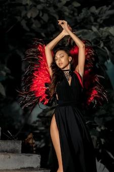 Koncepcja kusicielki. kobieta na namiętnej twarzy gra rolę. dziewczyna seksowny demon w czarnej sukni z czerwonymi skrzydłami, diabeł pełen pożądania stojący na schodach