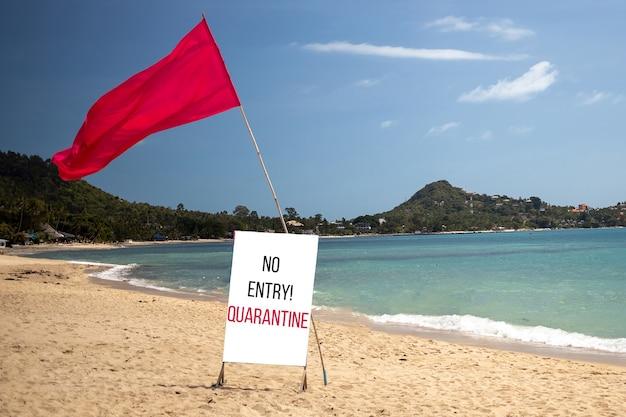 Koncepcja kwarantanny, zamknięte granice, anulowanie wakacji. tropikalna plaża w słoneczny dzień bez ludzi. jest czerwona flaga i tabliczka informująca o zakazie kwarantanny wjazdowej.