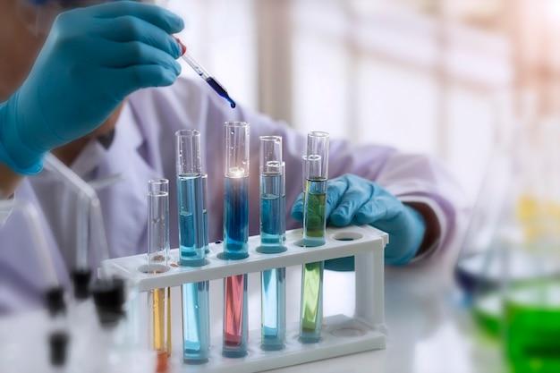 Koncepcja laboratorium; naukowcy używają wkraplacza do przeniesienia odczynnika chemicznego do probówki. obserwuje reakcję chemiczną w laboratorium.