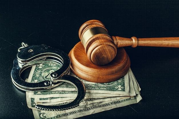 Koncepcja łapówki. banknoty dolarowe, kajdanki i młotek na ciemno czarnym stole