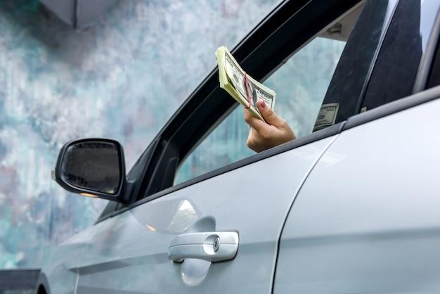 Koncepcja łapówki. kobiece ręce dając pakiet dolara wewnątrz samochodu z bliska