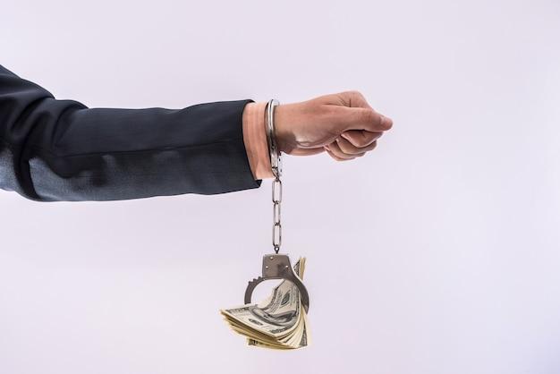 Koncepcja łapówki lub korupcji męskie ręce trzymają banknoty dolarowe w kajdankach. kryminalista