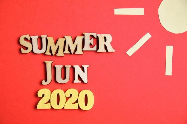 Koncepcja lato - czerwiec w nowym roku. drewniane liczby 2020 z literami i abstrakcyjnym słońcem.