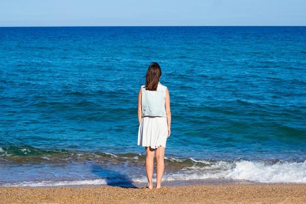 Koncepcja lato i podróże - widok kobiety stojącej na plaży z tyłu