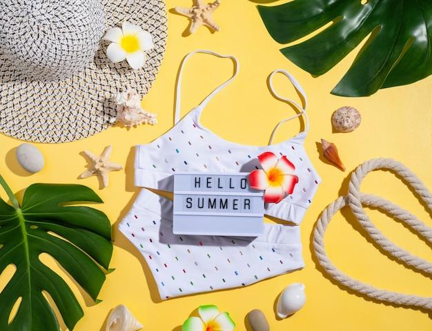 Koncepcja lato i wakacje. słowa hello summer na lightboxie z kostiumem kąpielowym, tropikalnymi liśćmi i muszelkami płasko leżały na pomarańczowym tle