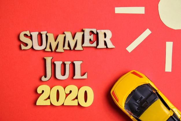 Koncepcja lato - lipiec w nowym roku. drewniane liczby 2020 z literami i abstrakcyjnym słońcem