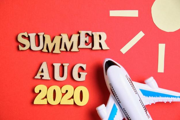 Koncepcja lato - sierpień w nowym roku. drewniane liczby 2020 z literami i streszczenie słońce, samolot.