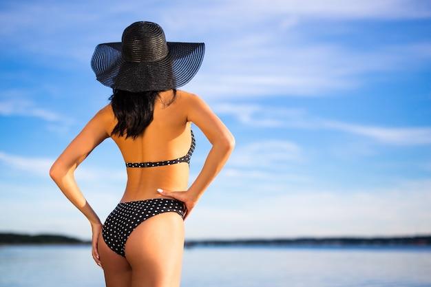 Koncepcja lato - widok z tyłu seksownej szczupłej kobiety w bikini pozowanie na plaży