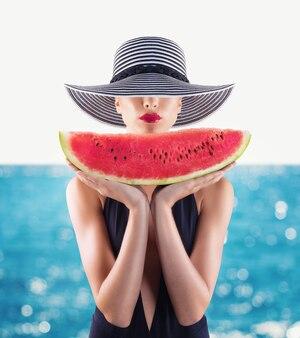 Koncepcja lato z dziewczyną z kostiumem kąpielowym i arbuzem