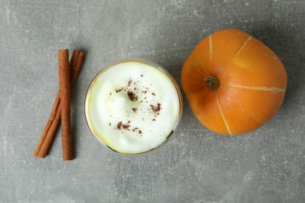 Koncepcja latte z dyni na szarym teksturowanym stole