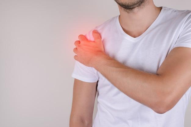 Koncepcja leczenia leczenia chorych. smutny zdenerwowany zestresowany nieszczęśliwy mężczyzna dotykający ramienia na szarym szarym tle kopii przestrzeni