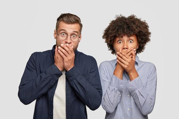 Koncepcja lęku i szoku. wzruszające, oszołomione przyjazne, mieszane rasy młode kobiety i mężczyźni zakrywają usta palmami