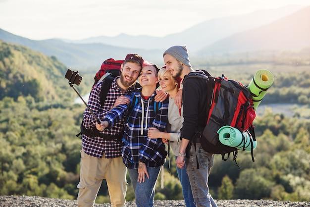 Koncepcja letnich podróży. szczęśliwi przyjaciele używa papierową mapę blisko wynajętego samochodu w naturze.