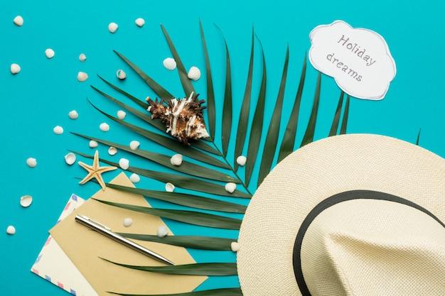 Koncepcja letnich wakacji. męska czapka i gałąź palmowa na jasnym tle