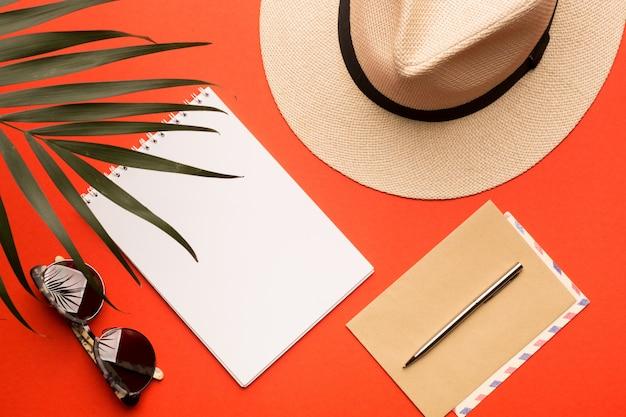 Koncepcja letnich wakacji. męska czapka, okulary przeciwsłoneczne, pocztówka, koperta, długopis i gałąź palmowa na jasnym koralowym tle