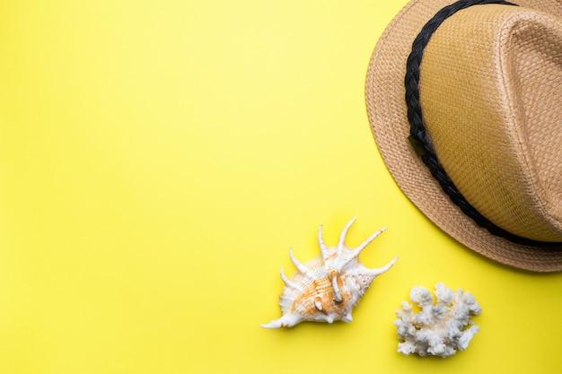 Koncepcja letnie wakacje. słomkowy kapelusz i skorupy na żółtym tle. skopiuj miejsce.