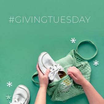 Koncepcja leżała płasko z rękami pakującymi buty i ubrania w siatkowej torbie. daj towary w dawanie wtorku, uczestnicząc w napędzie darowizn. zbieraj niechciane towary i przekaż je potrzebującym.