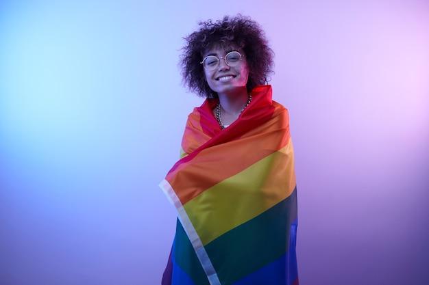 Koncepcja lgbtq. pozytywna dziewczynka kaukaski z afro kręcone włosy, trzymając tęczową flagę na białym tle