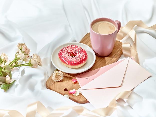 Koncepcja listu miłosnego na stole z kopertą, kawą, ciastem, kwiatami