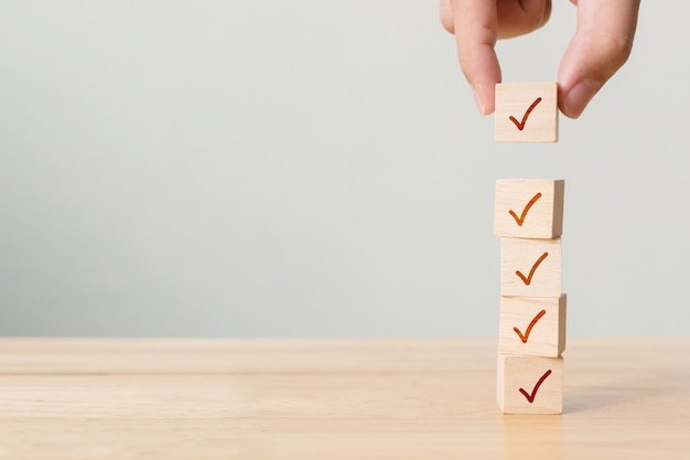 Koncepcja listy kontrolnej, znacznik wyboru na drewnianych klockach na stole z miejscem na kopię
