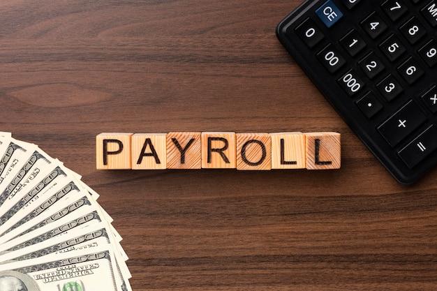 Koncepcja listy płac z widokiem z góry z gotówką i kalkulatorem