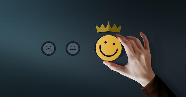 Koncepcja lojalności klienta. doświadczenia klientów. zadowolony klient dający pozytywną ocenę usług za satysfakcję prezentowaną przez uśmiechniętą twarz i koronę