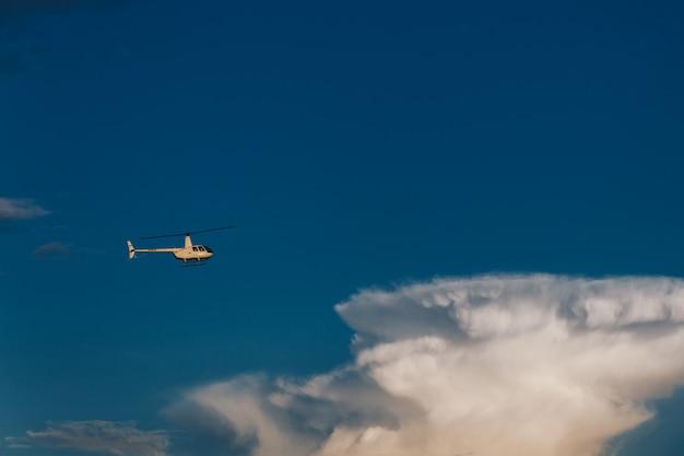 Koncepcja lotu, lotnictwa i transportu. horyzontalny strzał biały helikopter lata wysoko w niebieskim niebie z chmurami