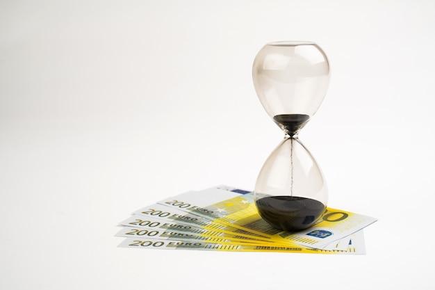 Koncepcja lub koncepcyjne banknot euro papierowe pieniądze na tle klepsydry lub czasu, metafora do biznesu