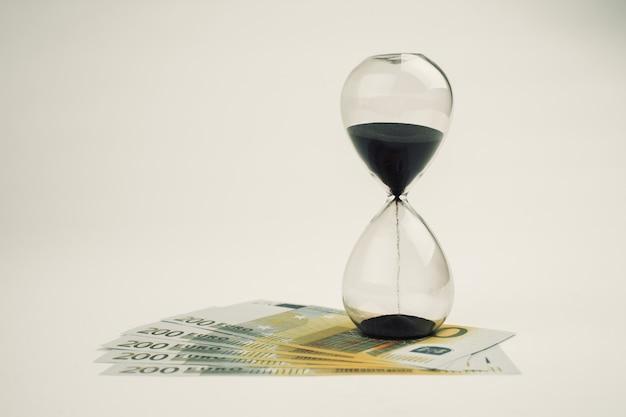Koncepcja lub koncepcyjny banknot euro z papierowymi pieniędzmi na tle klepsydry lub czasu, metafora biznesu, finansów, pożyczki, sukcesu, bogactwa, bankowości, ekonomii, zysku lub handlu, długu, straty lub wizji