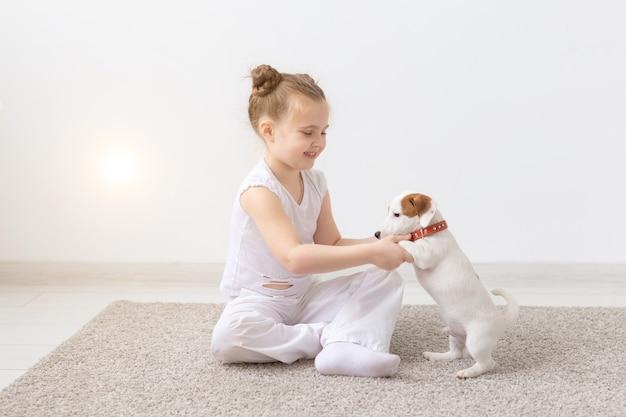 Koncepcja ludzi, dzieci i zwierząt domowych - mała dziewczynka siedzi na podłodze z uroczym szczeniakiem jack russell terrier