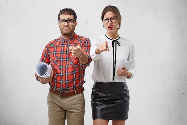 Koncepcja ludzi, emocji i pracy. niezadowolony młody brodaty mężczyzna w kwadratowych okularach i kobieta o pociągającym wyrazie
