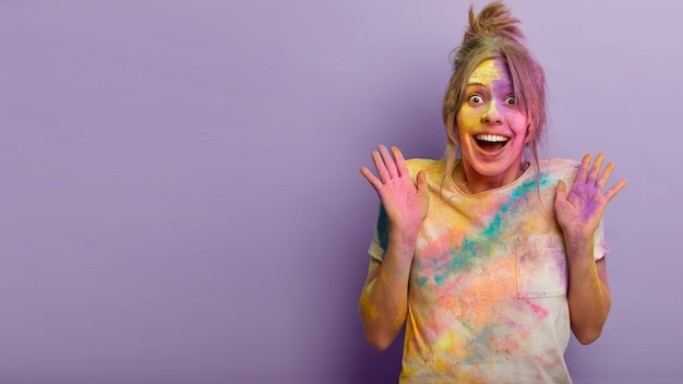 Koncepcja ludzi, emocji i wakacji. pełna emocji szczęśliwa europejka podnosi dłonie ze szczęścia, nie może powstrzymać pozytywnych uczuć, będąc pod wrażeniem obchodów holi festival of colours za granicą