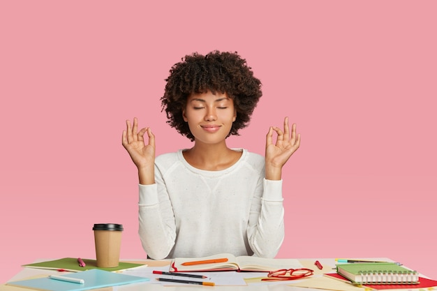 Koncepcja ludzi, harmonii i pracy. zadowolona ciemnoskóra kobieta z fryzurą w stylu afro, medytuje w miejscu pracy, ma zamknięte oczy