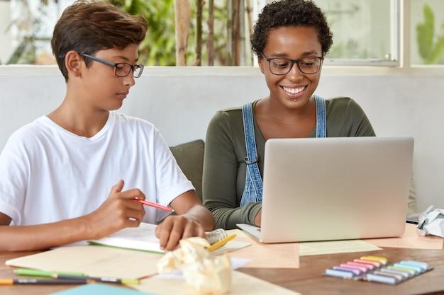 Koncepcja ludzi i coworkingu. młodzież z mieszanej rasy pracuje w szkolnym projekcie