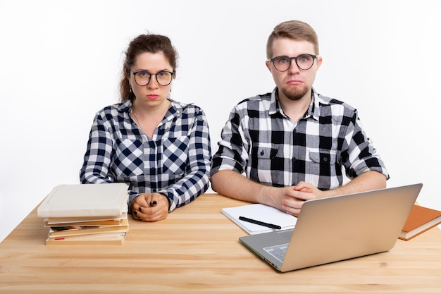 Koncepcja ludzi i edukacji dwóch smutnych studentów ubranych w koszulę w kratę siedzi przy stole