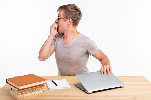 Koncepcja ludzi i edukacji zabawny student mężczyzna siedzi przy drewnianym stole z laptopem i książkami