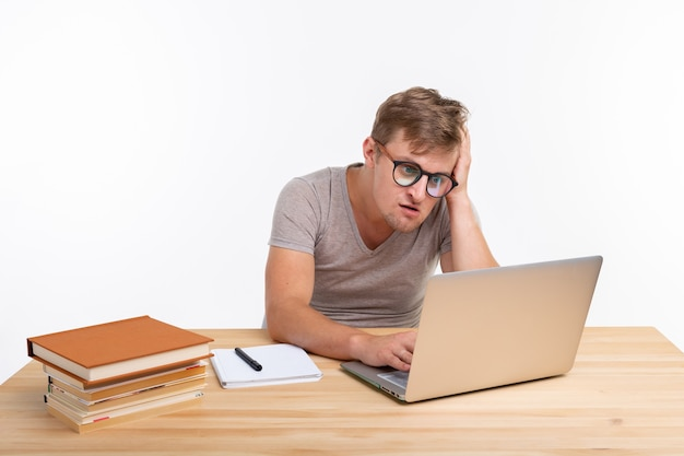 Koncepcja ludzi i edukacji zaintrygowany student siedzi przy drewnianym stole z laptopem