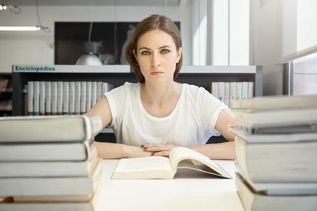 Koncepcja ludzi i edukacji. zmęczona studentka studiująca, czytająca podręcznik ekonomii, przygotowująca się do testu lub egzaminu mba, uczucie wyczerpania, siedzenie przy biurku w bibliotece
