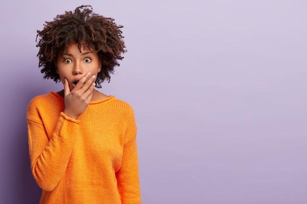 Koncepcja ludzi i emocji. zszokowana przerażona kobieta zakrywa szeroko otwarte usta, słyszy straszną plotkę