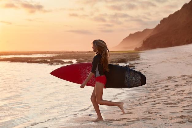Koncepcja ludzi i podróży. ujęcie szczupłego surferki o idealnej figurze