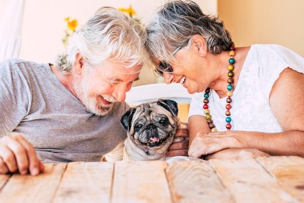 Koncepcja ludzi i psa z parą szczęśliwej pary starszych dojrzałych mężczyzn i kobiet uśmiechających się i bawiących się ze swoim małym szczeniakiem mopsem