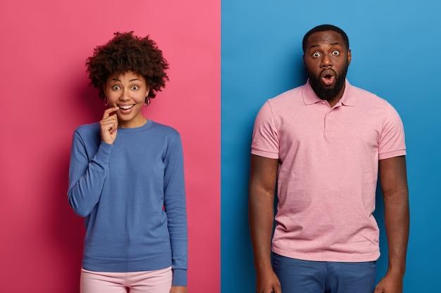Koncepcja ludzi i reakcji. uśmiechnięta, ciekawa ciemnoskóra kobieta i wstrząśnięty emocjonalnie mężczyzna stoją obok siebie
