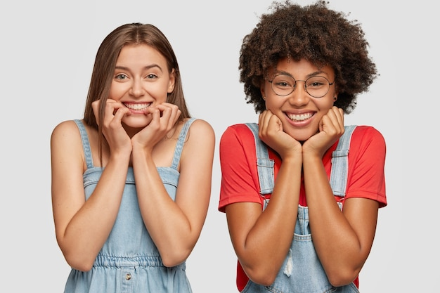 Koncepcja ludzi i różnorodności. wesołe kobiety rasy mieszanej trzymają podbródki, mają zębate uśmiechy