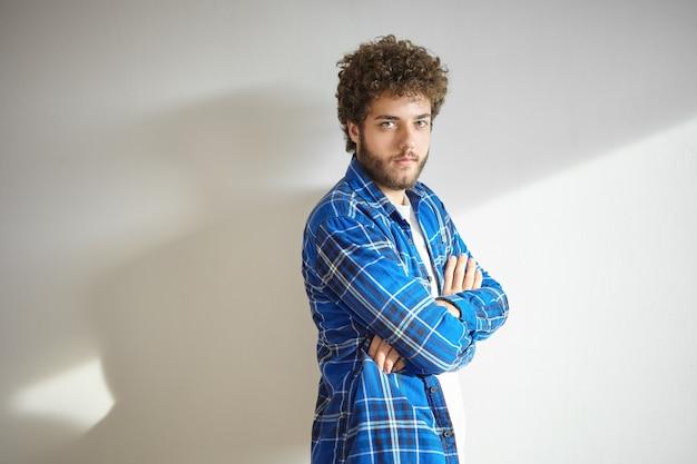 Koncepcja ludzi i stylu życia. portret modny młody brodaty mężczyzna ubrany w stylową kraciastą koszulę z założonymi rękami, z poważnym wyrazem twarzy