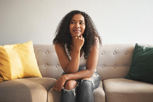 Koncepcja ludzi i stylu życia. portret wesołej, wspaniałej młodej kobiety afro american w stylowych dżinsach spędzających czas w domu, siedząc na wygodnej kanapie, odwracając wzrok z rozmarzonym uśmiechem