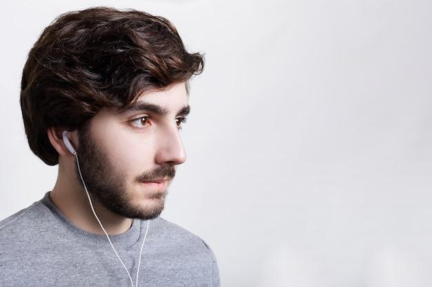 Koncepcja ludzi i stylu życia. z ukosa portret przystojny młody brodaty mężczyzna nosi szary sweter