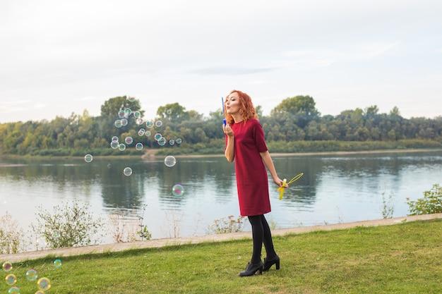 Koncepcja ludzi i zabawy młoda kobieta w czerwonej sukience dmuchanie baniek mydlanych w pobliżu jeziora