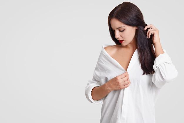 Koncepcja ludzi i zmysłowości. zamyślona urocza młoda brunetka kobieta patrzy w dół, trzyma rękę na swoich długich ciemnych włosach, nosi obszerną koszulę, stoi przy białej ścianie z miejsca na tekst