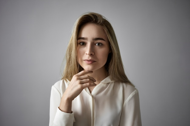 Koncepcja ludzi, kobiecości, piękna, stylu i mody. poziome ujęcie atrakcyjnej, jasnowłosej młodej kobiety rasy kaukaskiej z luźnymi włosami i piegami na brodzie, o poważnym, zamyślonym spojrzeniu
