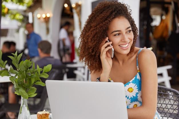Koncepcja ludzi, komunikacji i technologii. afroamerykanka przyjemnie rozmawia z przyjacielem za pośrednictwem smartfona